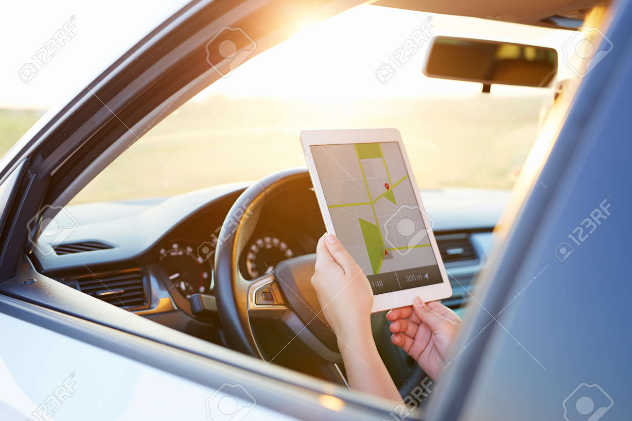 Woman in the car and holding tablet with map gps navigation,