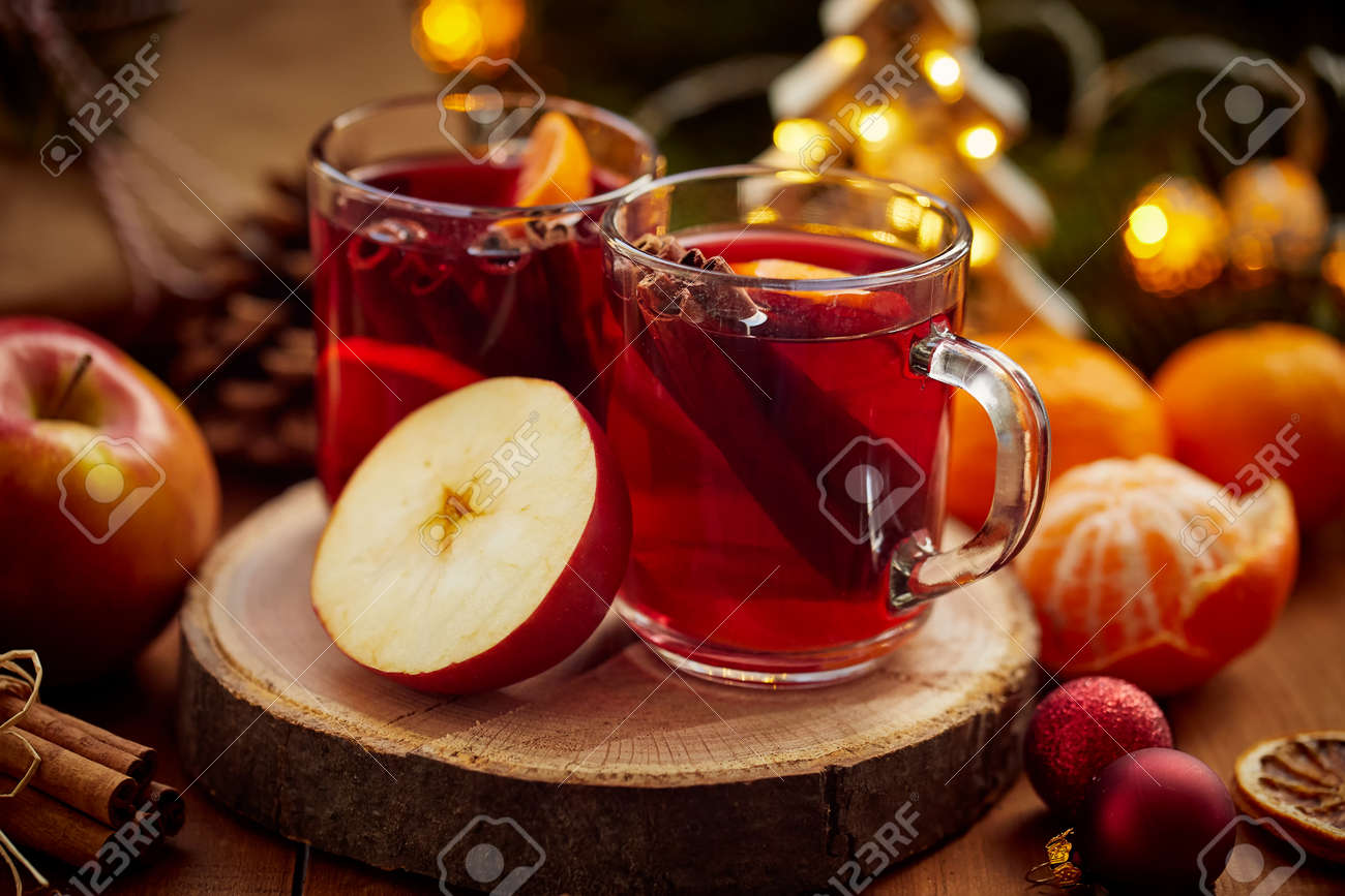 Two glasses of hot mulled wine and apple on christmas table - 135143577