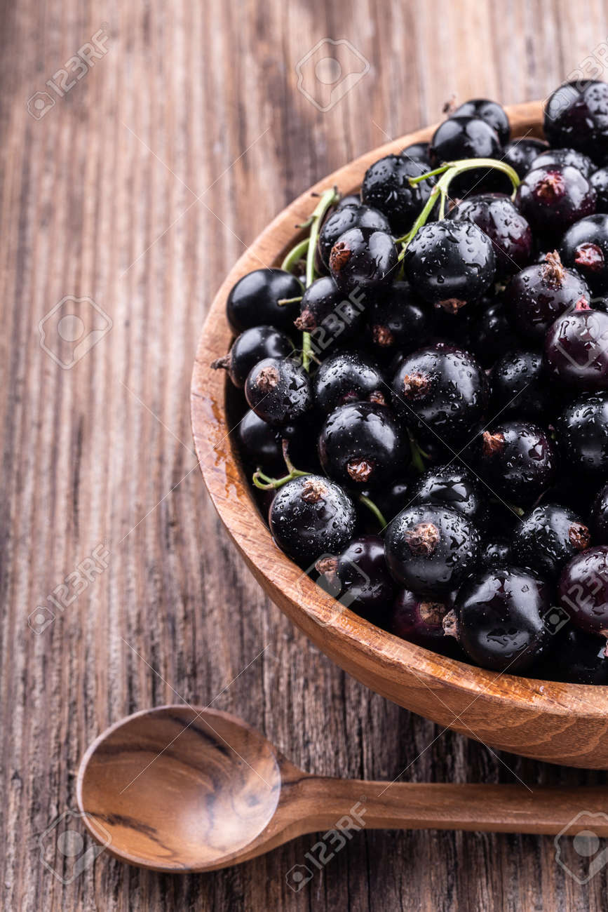 Half of big wooden bowl with fresh black currant and spoon on wooden background close-up top view . Healthy food, harvesting, vitamin, detox, vegan, vegetarian, alternative medicine. - 111517901