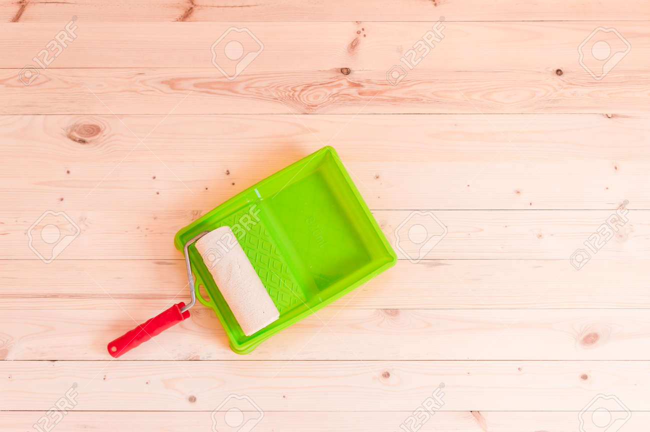 Paint roller brush on wooden table background - 104189839
