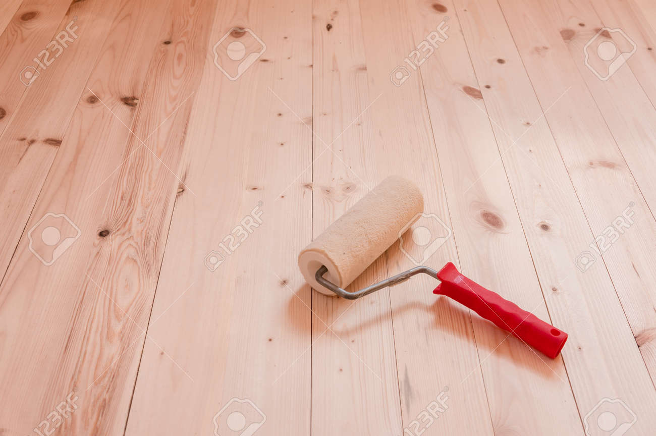 Paint roller brush on wooden table background - 104189840