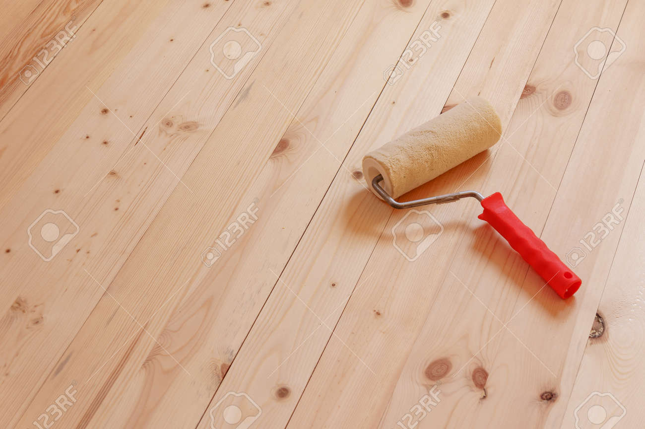 Paint roller brush on wood background - 104140566