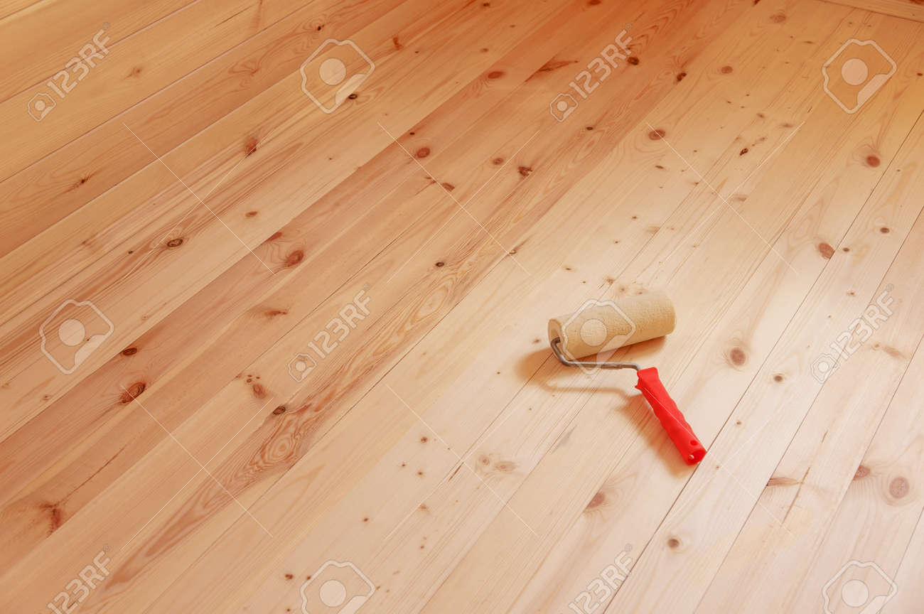 Paint roller brush on wood background - 104140567