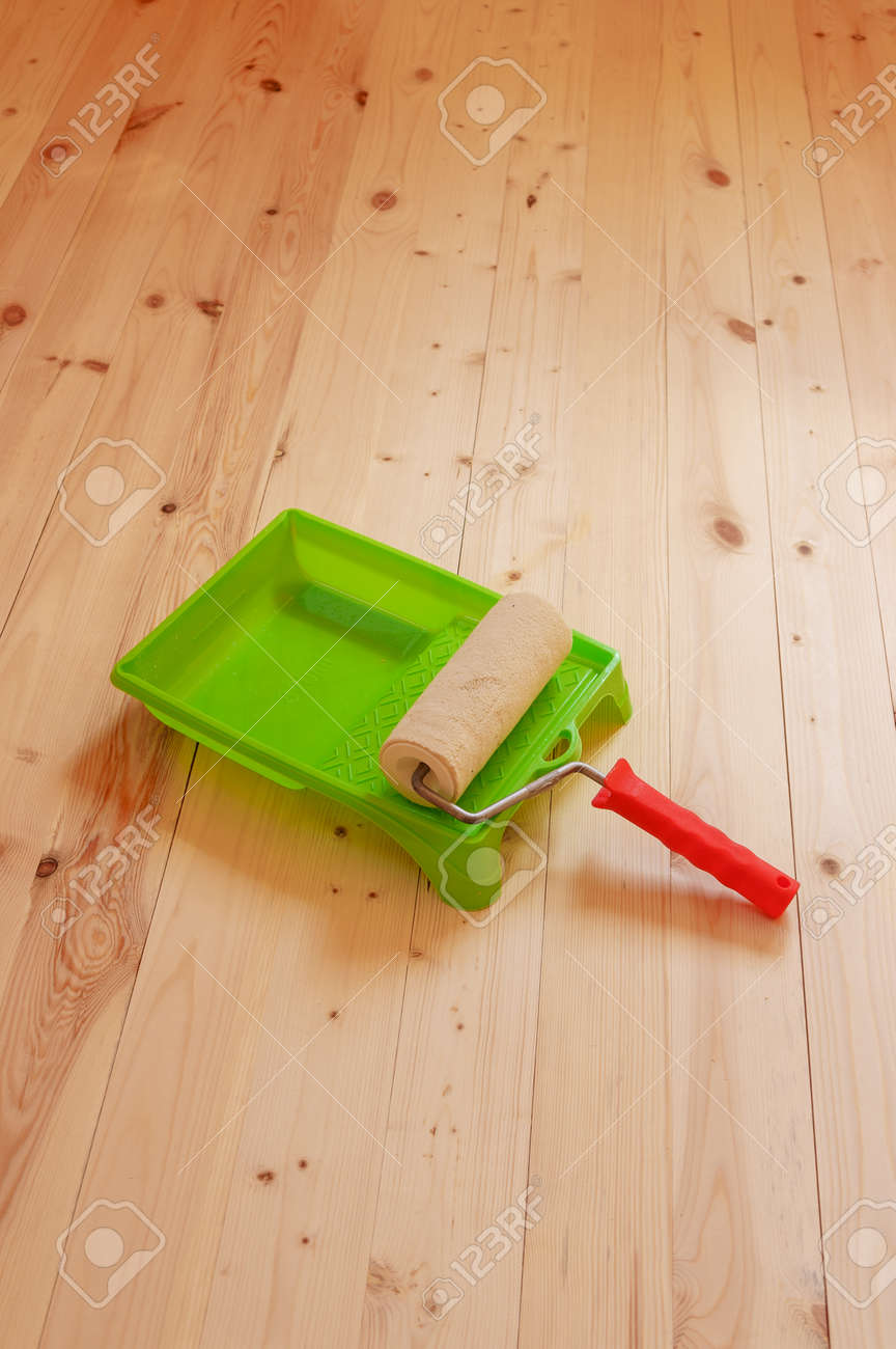 Paint roller brush on wood background - 104140568