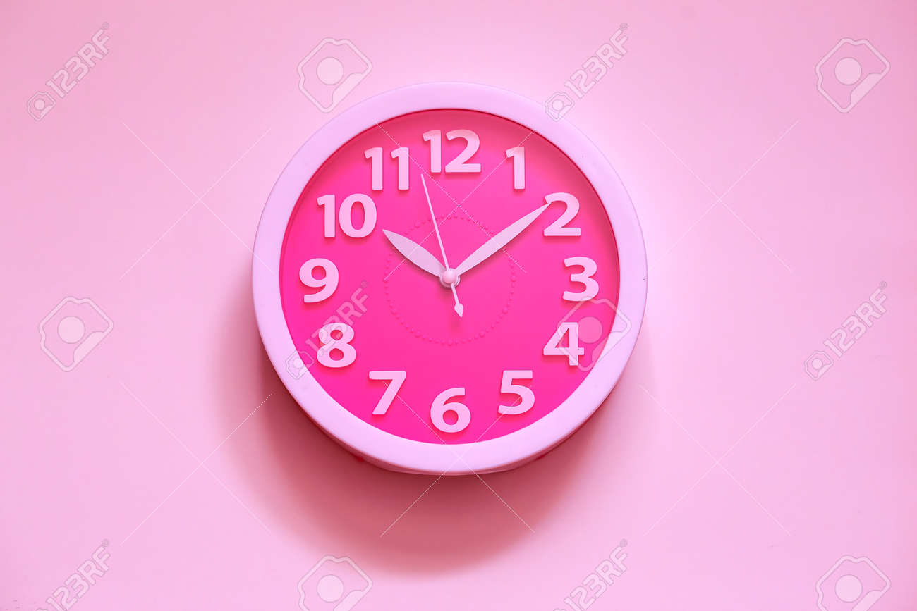 Pink clock on pink painted wall. Minimal time concept. Chrismas eve or new year idea. Stylish analog clock hanging on wall, space for text - 167623203