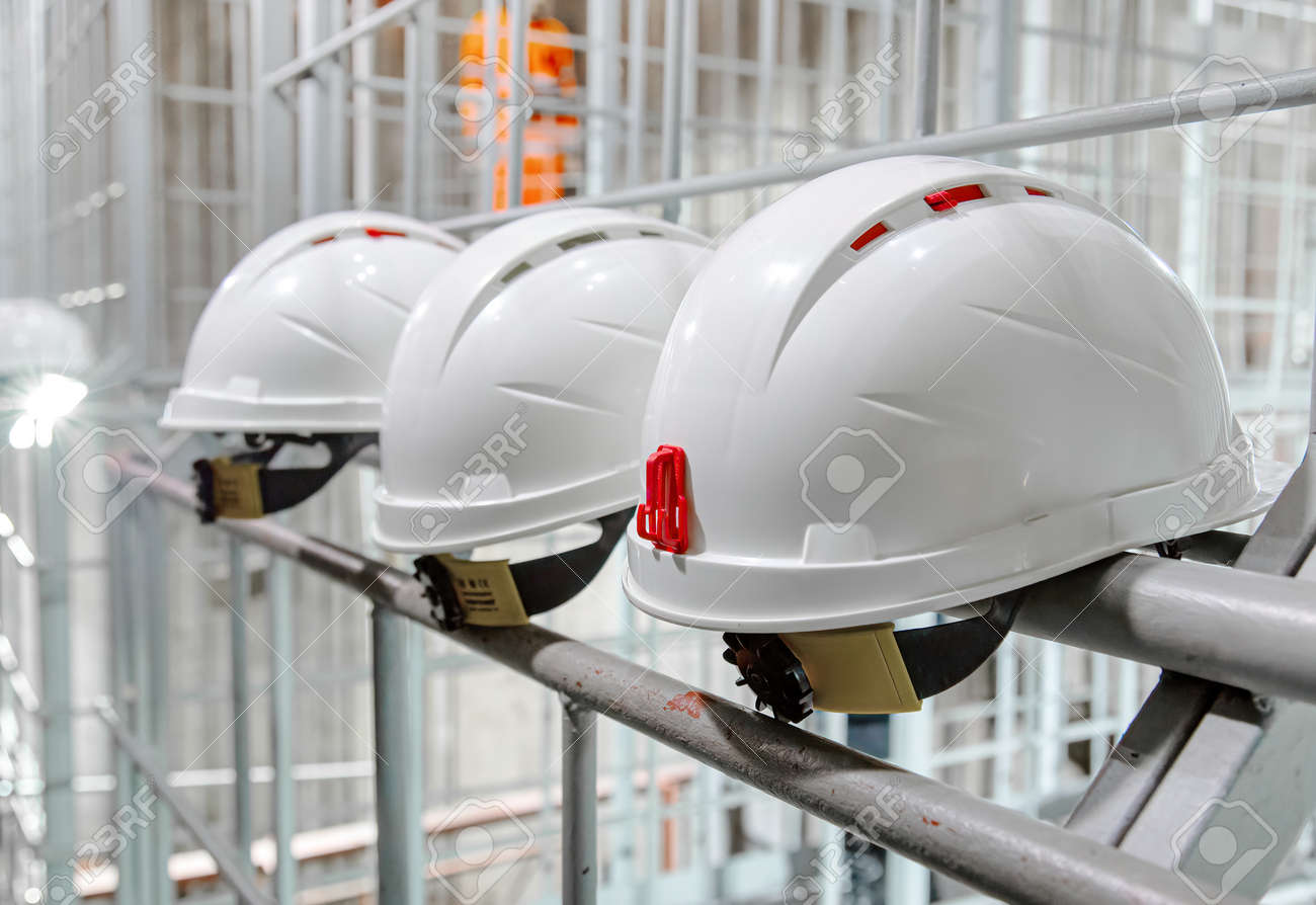 White safety helmets hanging on wall at the factory. Construction engineer safety white headgear - 169111917