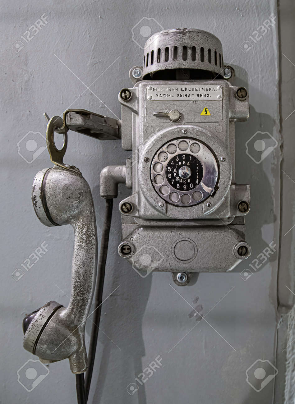 Old metal wall-mounted telephone with rotary dial. Antique phone with dial - 169111918