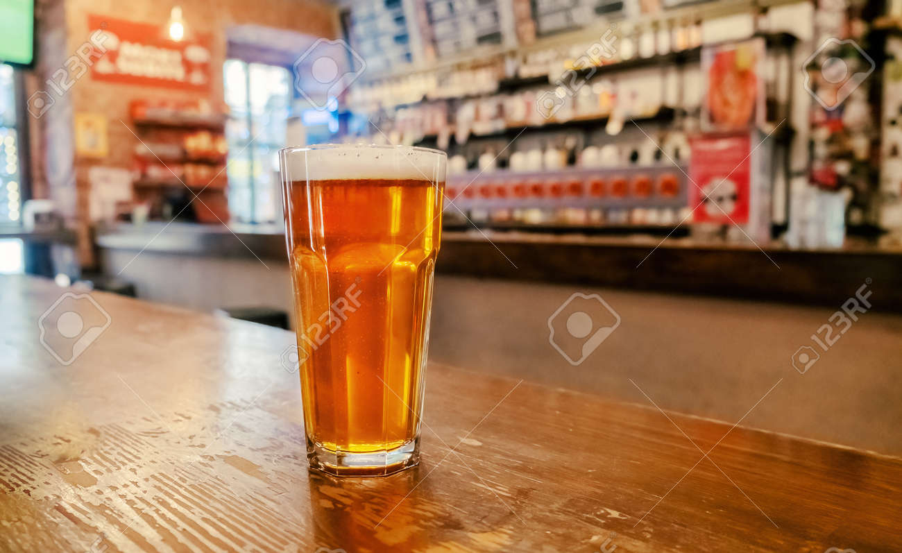 Beer glass on a bar table. Closeup - 169669200