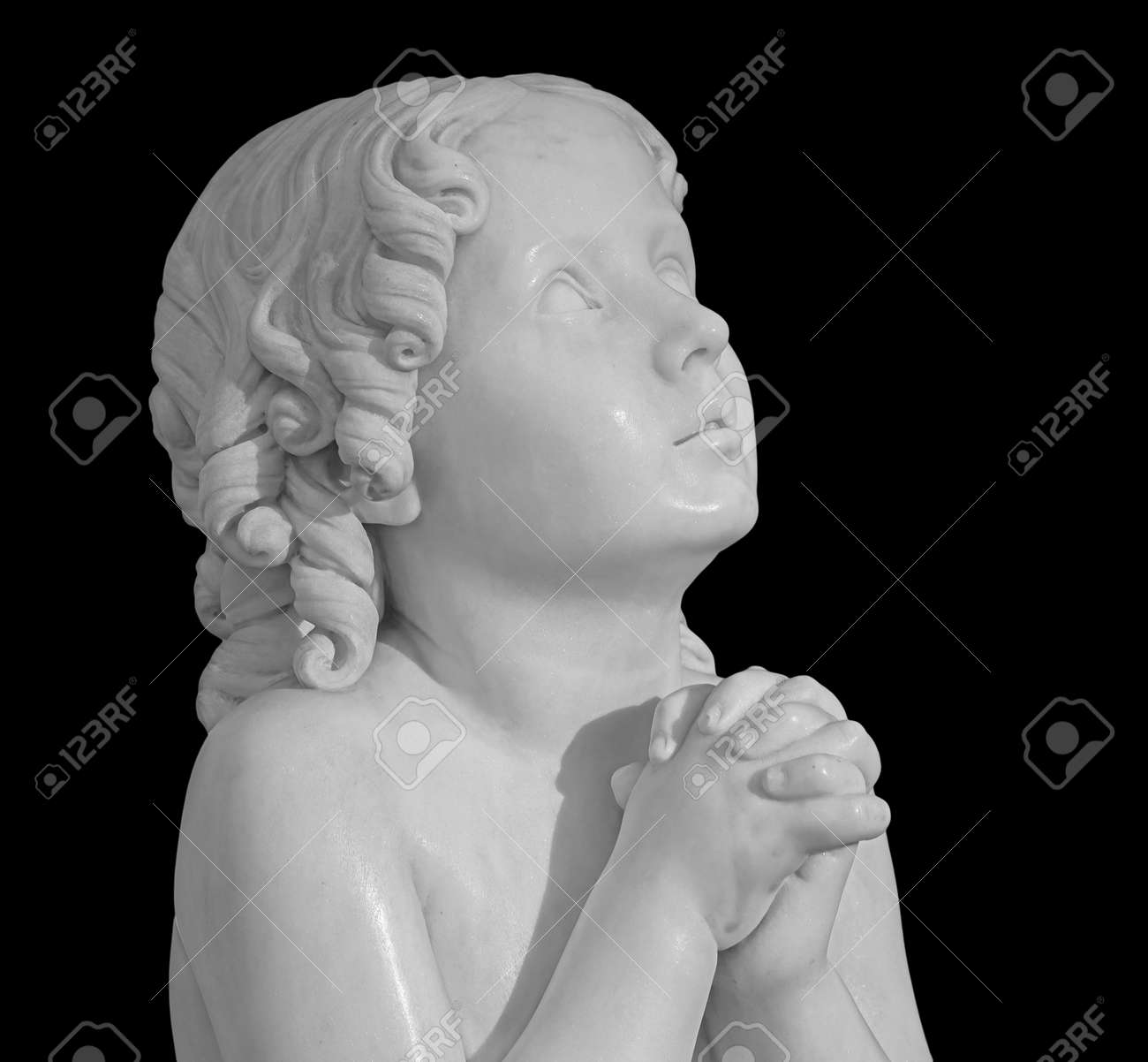 Beautiful marble statue of an pray infant angel isolated on black - 169669220