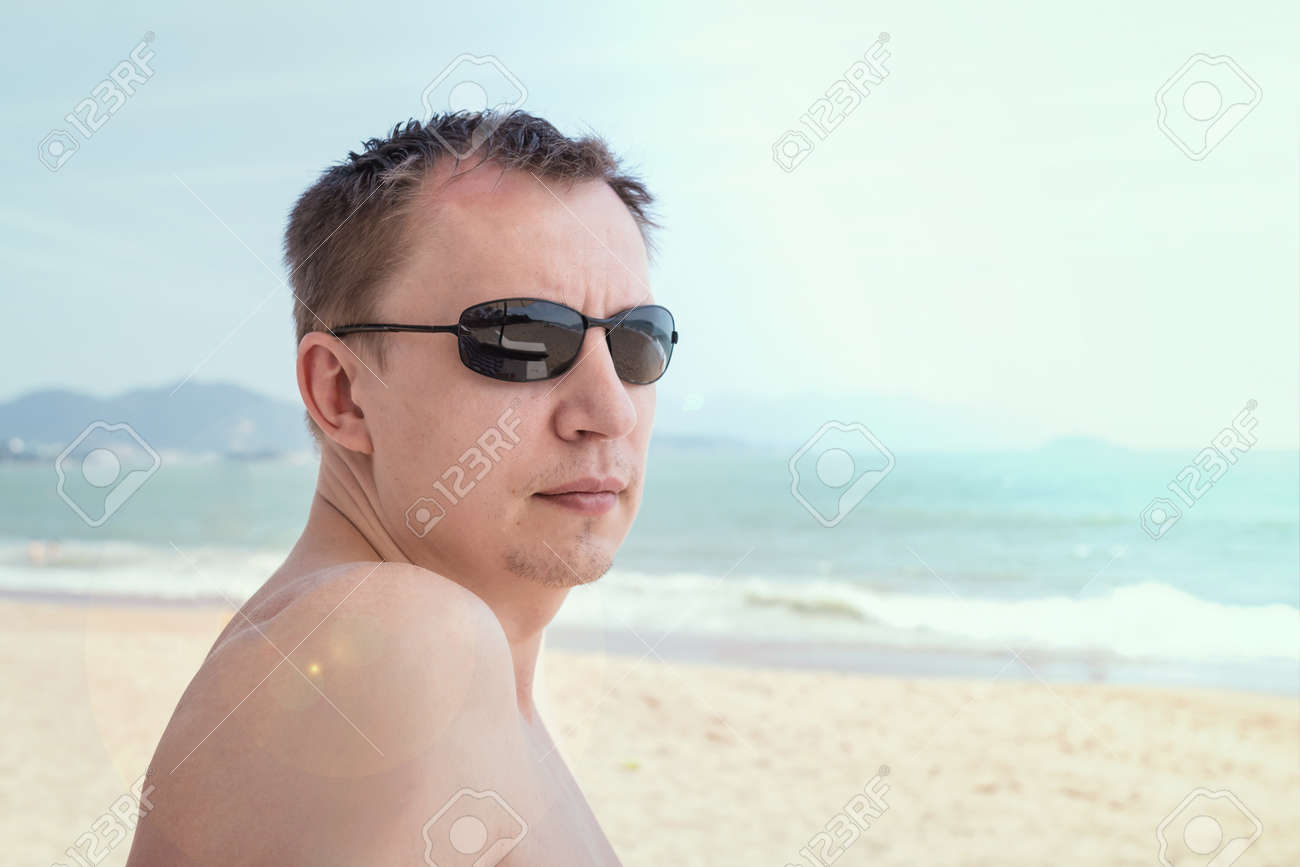 ddaa53e79967 Portrait of an attractive young man in sunglasses on a tropical beach Stock  Photo - 74053540
