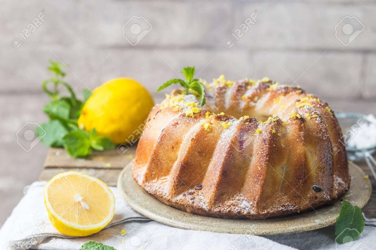 Homemade lemon bundt cake with icing sugar on a black background - 135326048