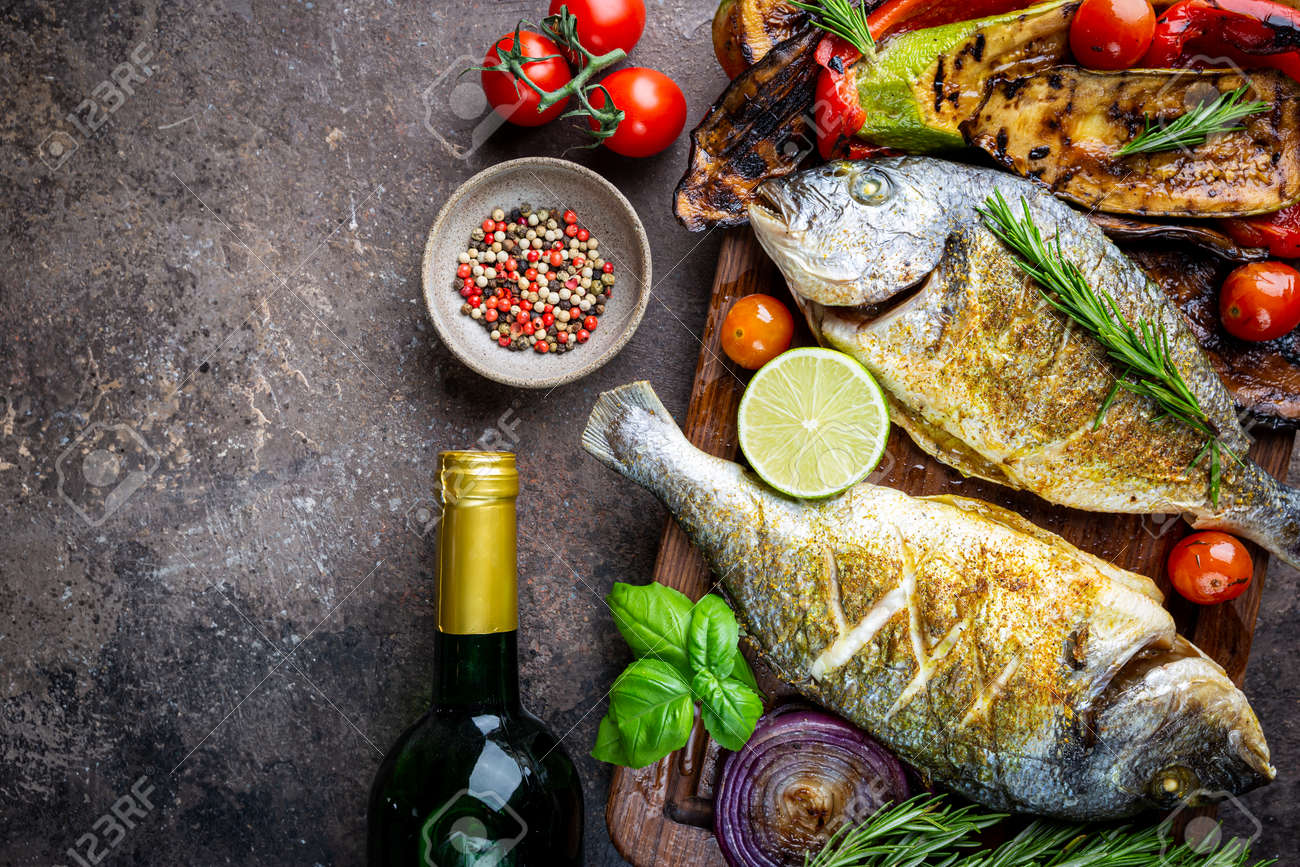 Baked Dorado fish, sea bream with grilled vegetables, herbs and seasonings, top view - 139377803