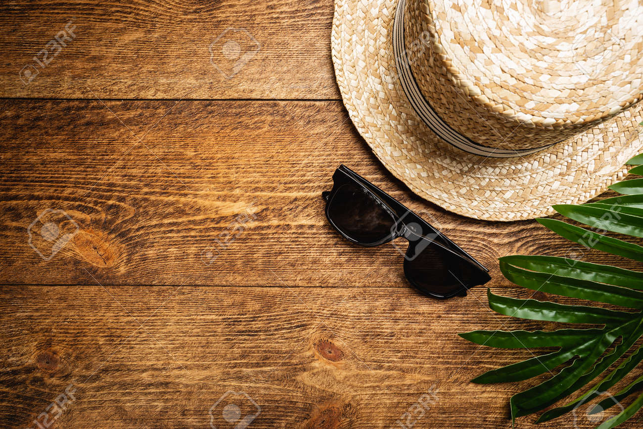 Straw beach hat and sun glasses top view on wooden background, summer flat lay - 153184967