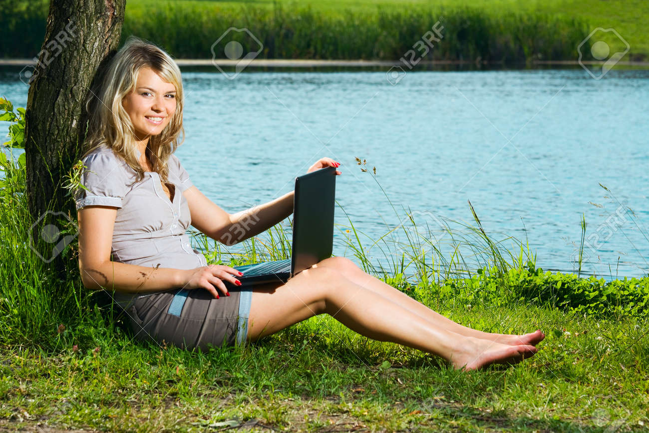 smiling girl with laptop, beautiful blonde woman sitting under a tree near the calm lake Stock Photo - 14796435