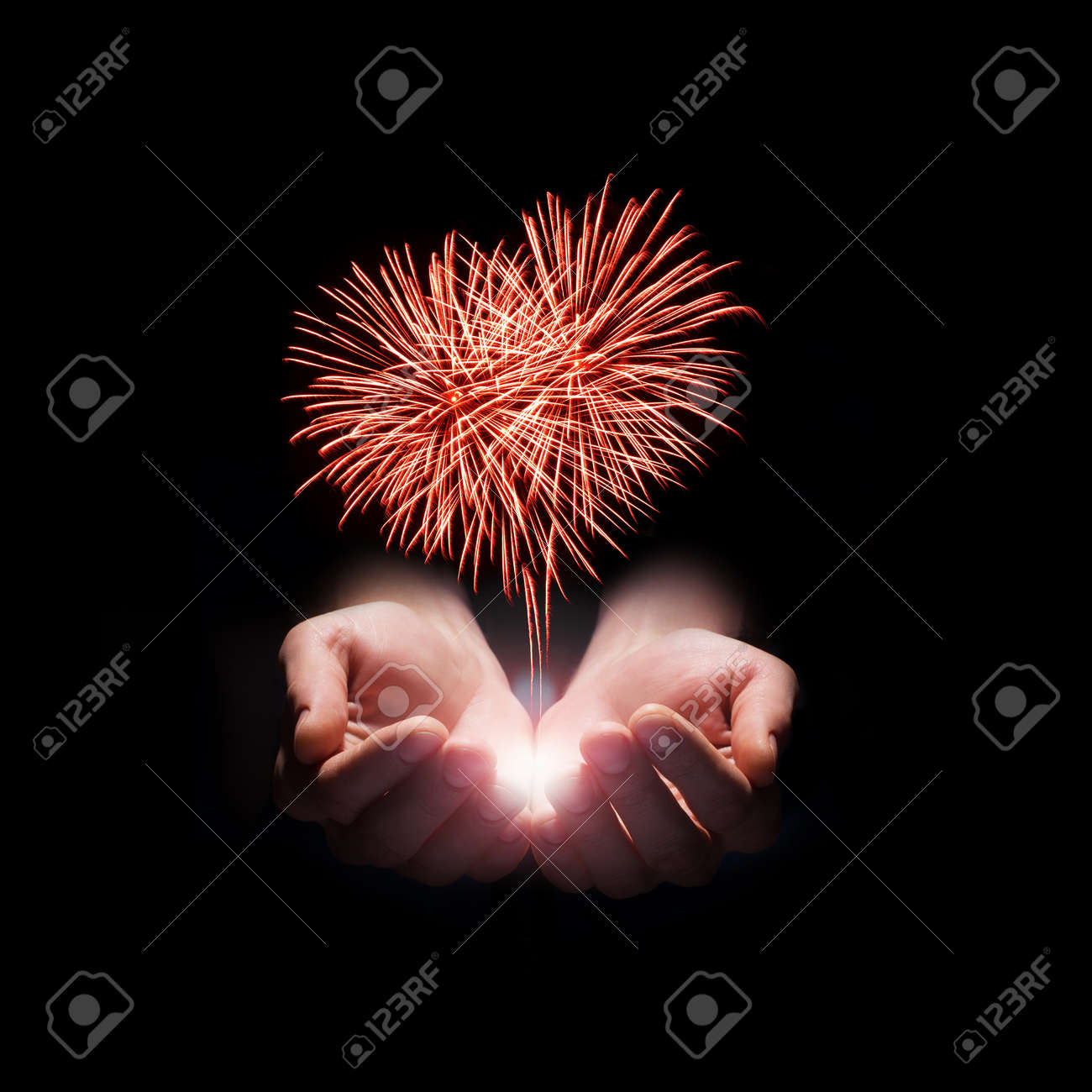 fireworks in the men's hands in the shape of a red heart on black background Stock Photo - 17845031