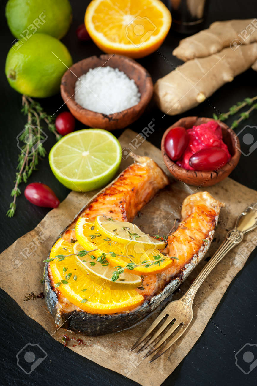 Grilled salmon with thyme on a dark background - 22995090