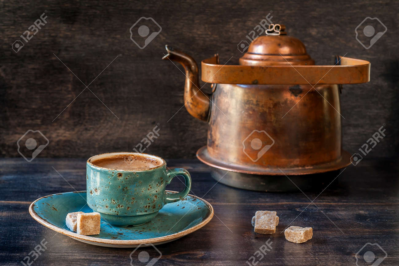Espresso coffee in a blue cup and old kettle on a wooden board - 25784770
