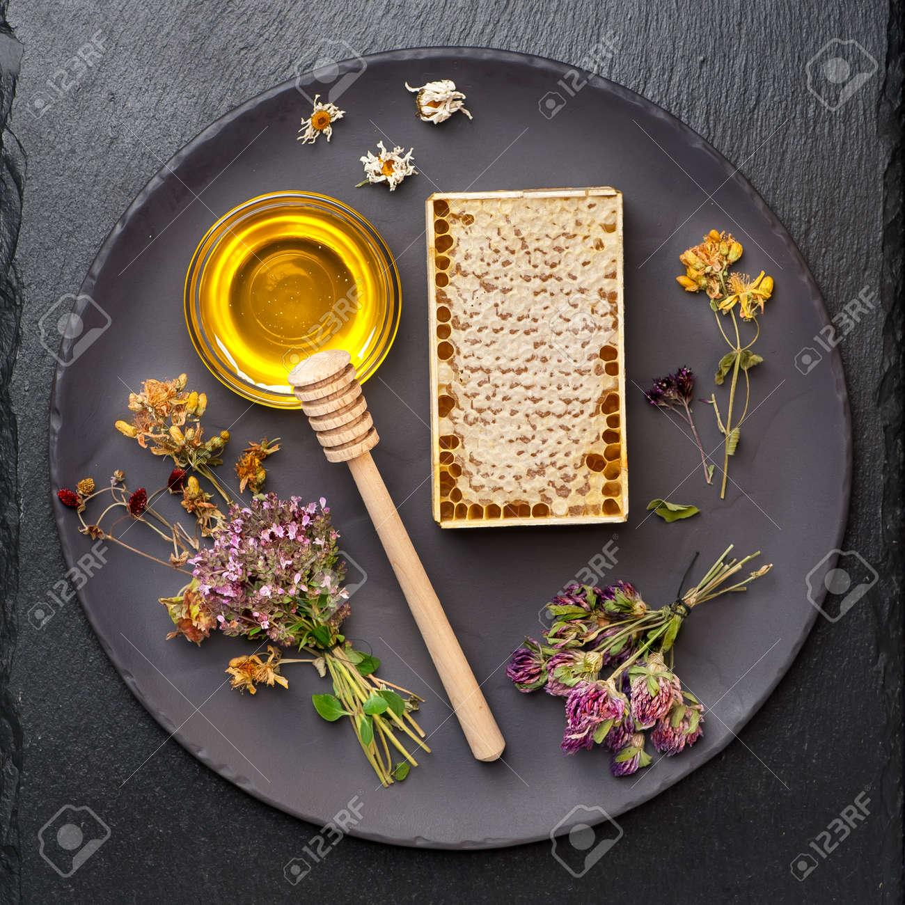 Honey, honeycomb and dried herbs on dark background - 32489614