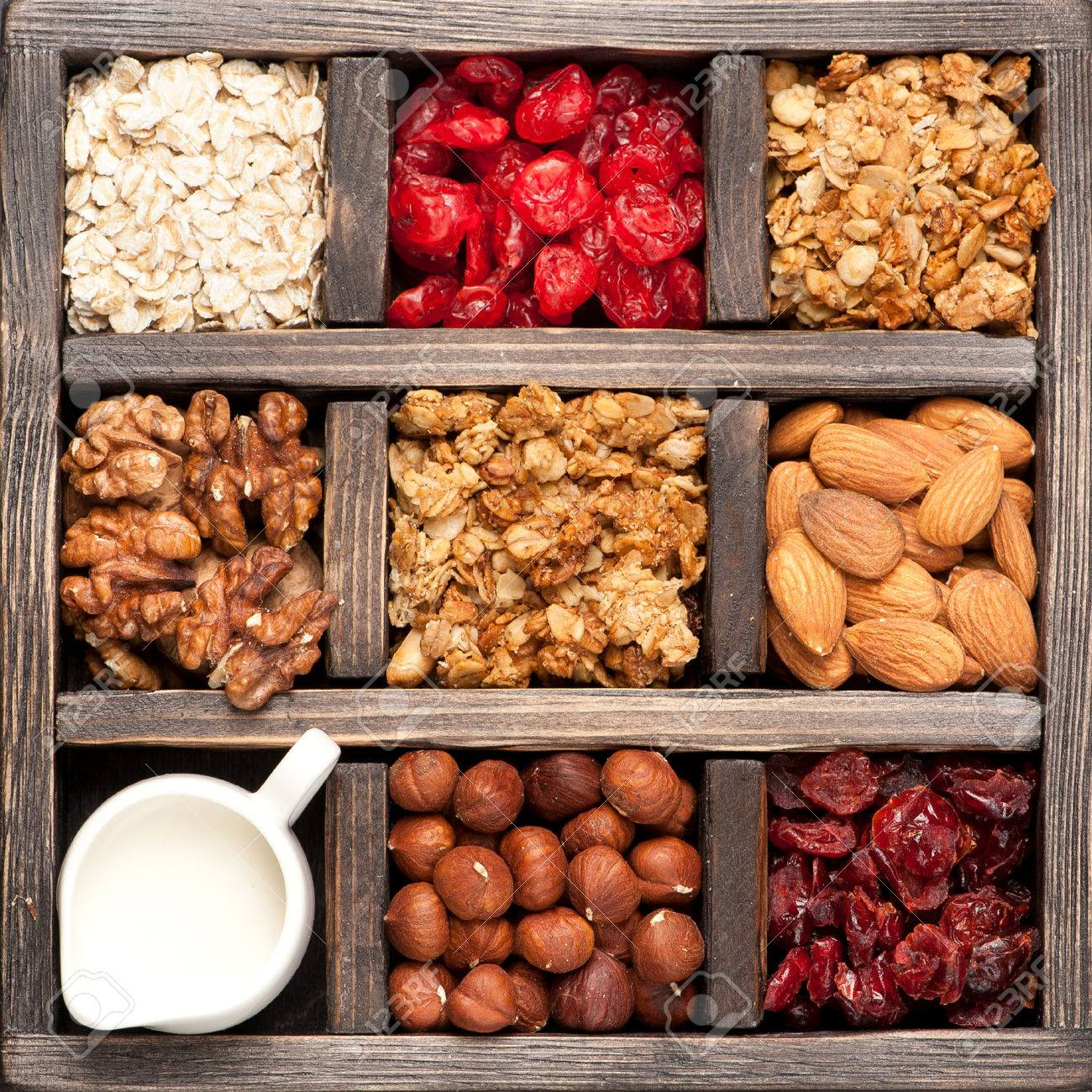 granola, oatmeal, nuts, berries in a wooden box. Top view. Food background - 38347910