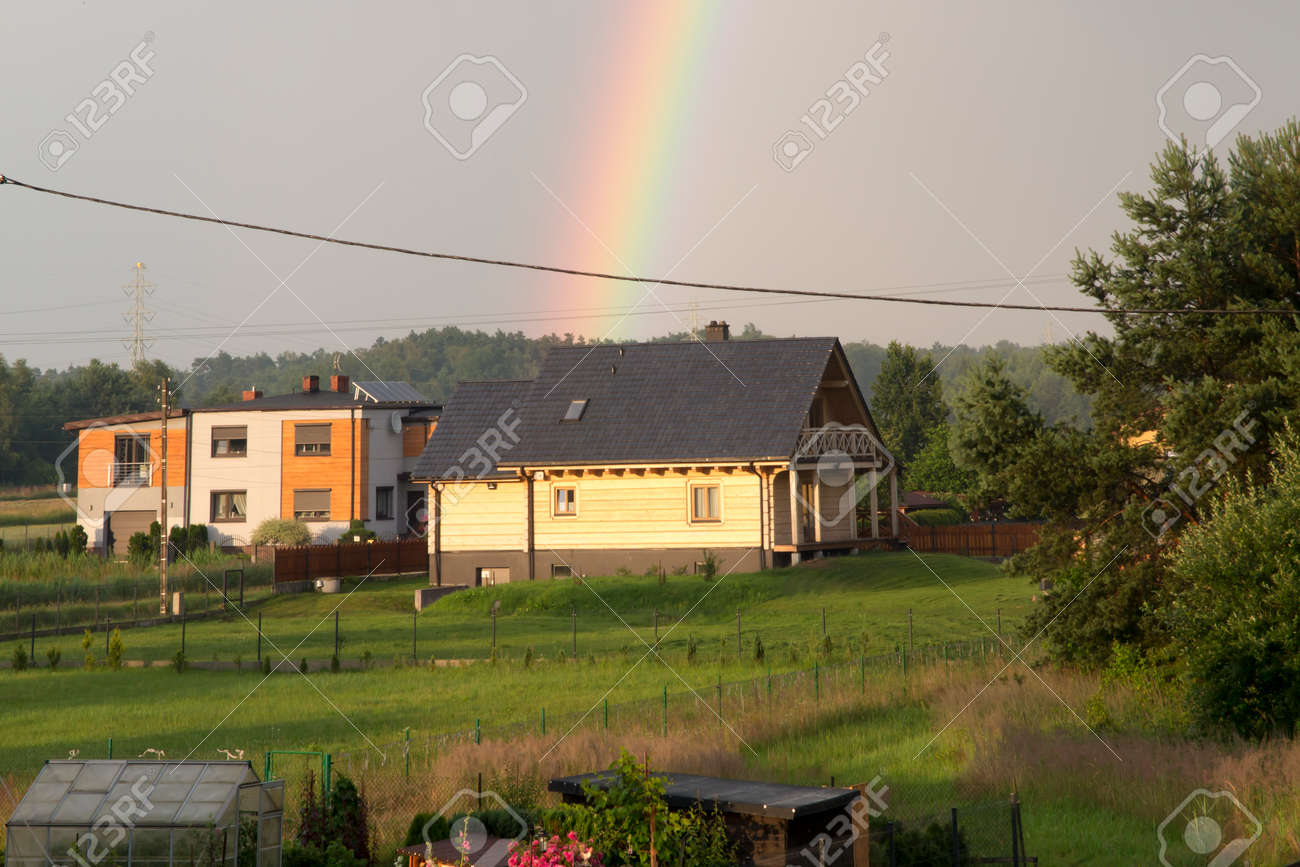 rainbow over a wooden house in a rural setting - 159707900