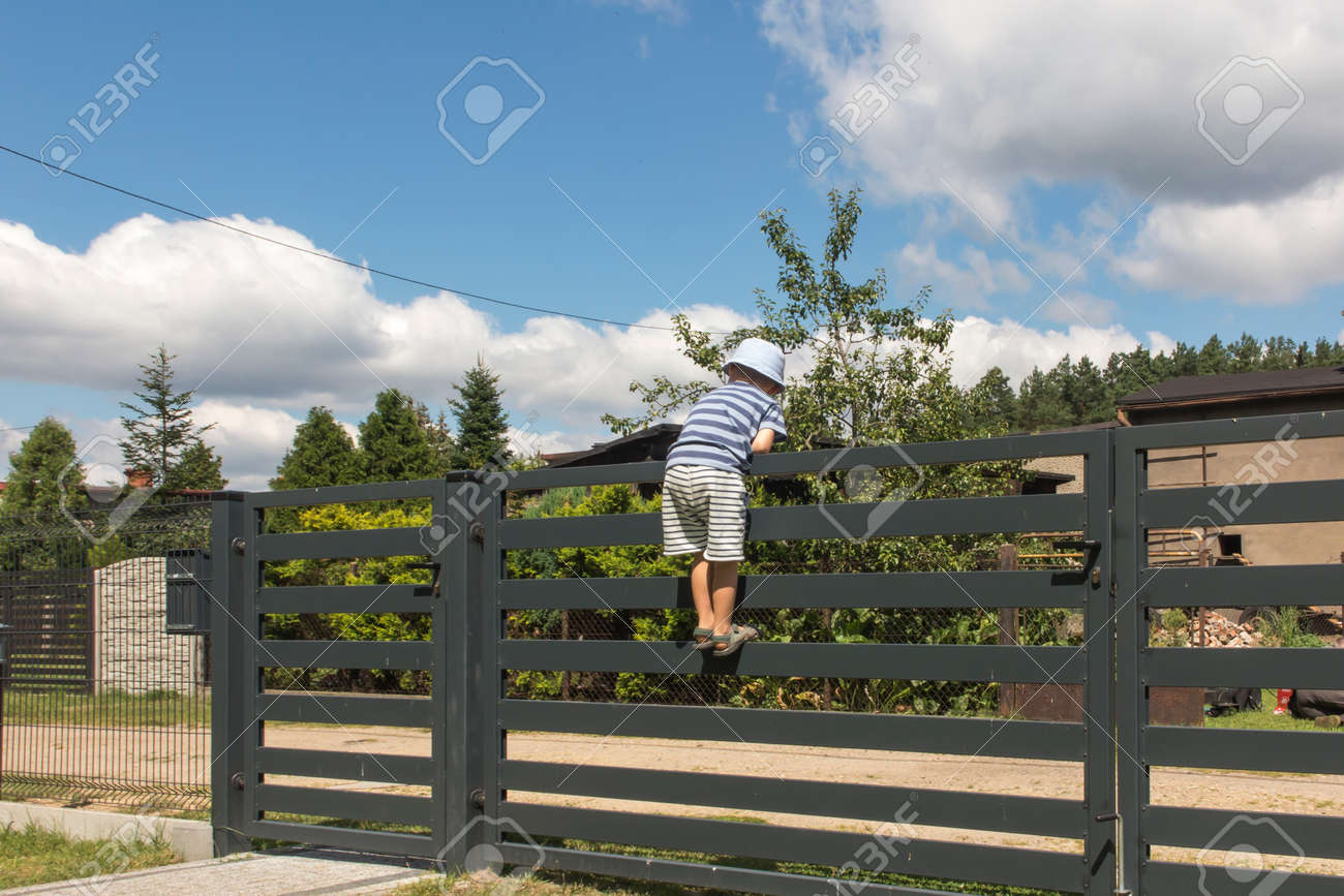 the boy watches the road after entering the gate in the fence - 158732569