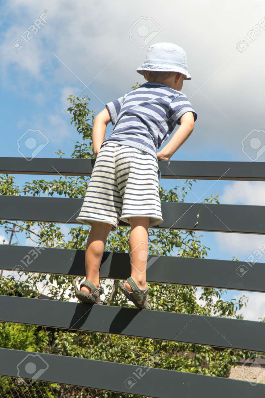 the boy watches the road after entering the gate in the fence - 158732704