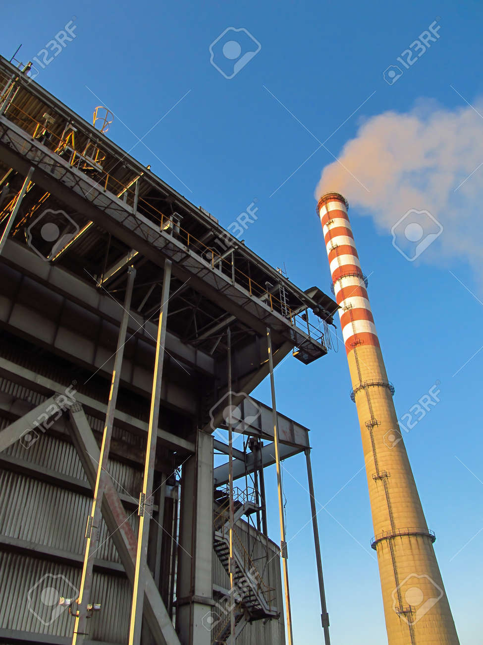 a tall, white and red chimney and a fragment of the power plant building - 157852224