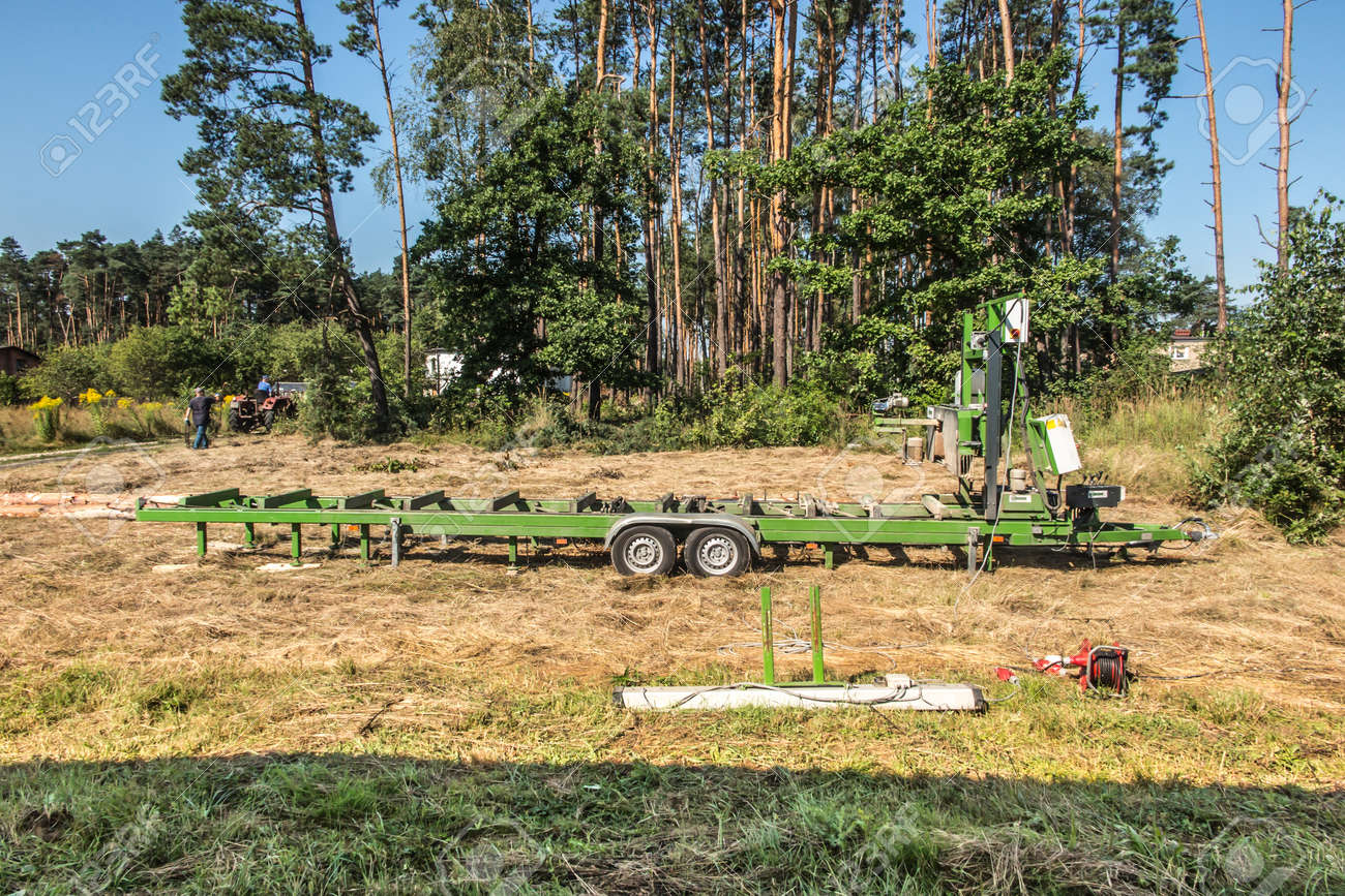 Mobile sawing equipment for logs in the open air. Rural landscape on a sunny day. Mobility and work speed - 157852359
