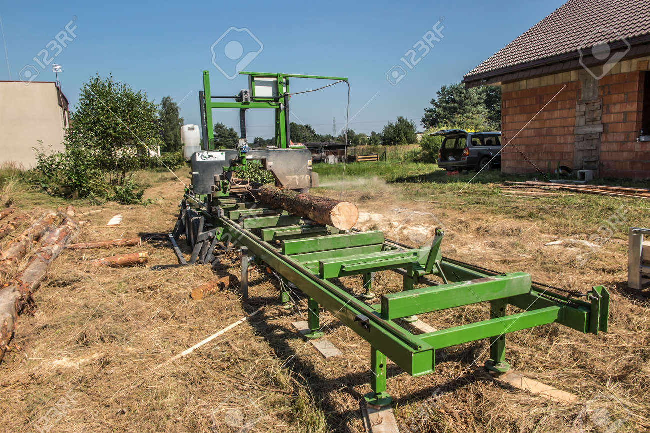 Mobile sawing equipment for logs in the open air. Rural landscape on a sunny day. Mobility and work speed - 157912277