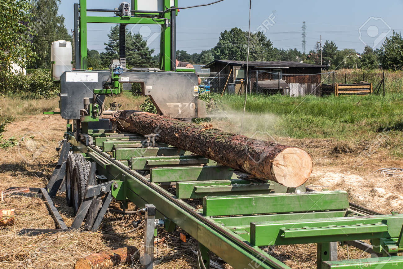 Mobile sawing equipment for logs in the open air. Rural landscape on a sunny day. Mobility and work speed - 157912281