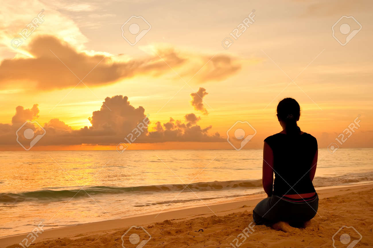 Woman sitting on a sand beach in front of sunset and ocean in summer Stock Photo - 9199547
