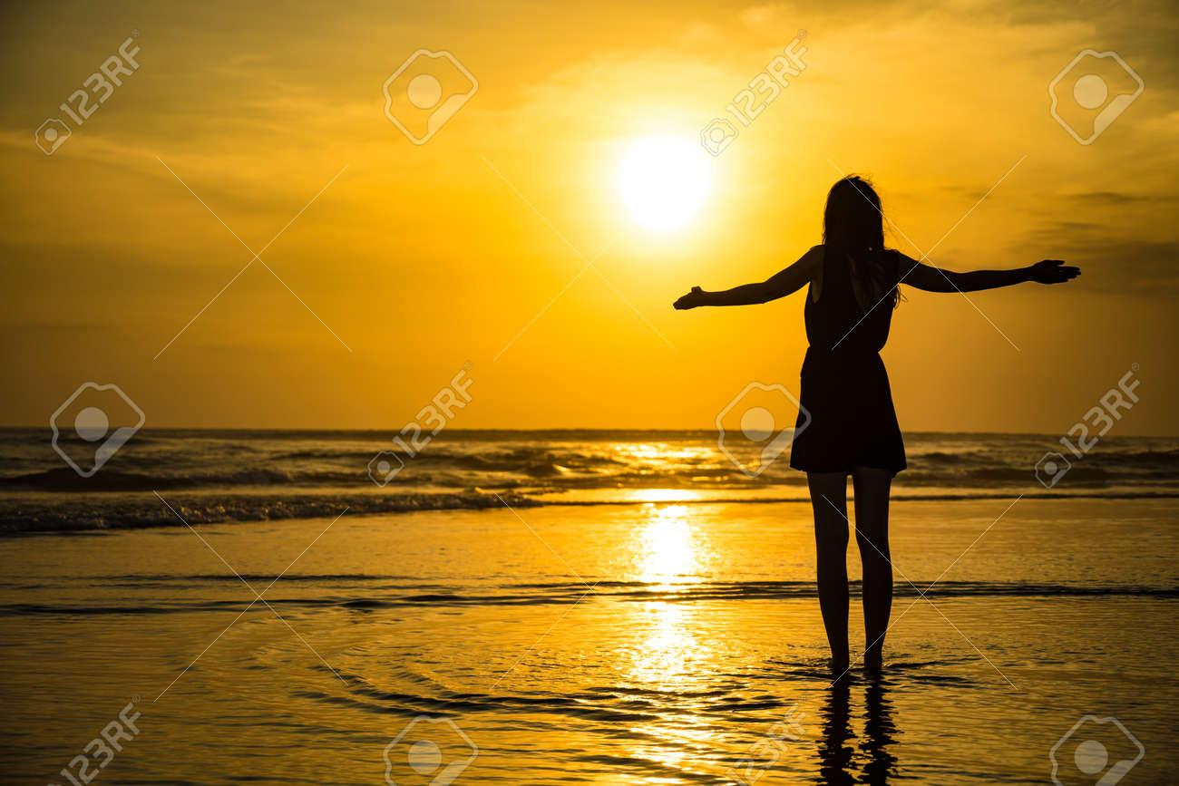 Woman Enjoying Beautiful Sunset in Bali - 135700400