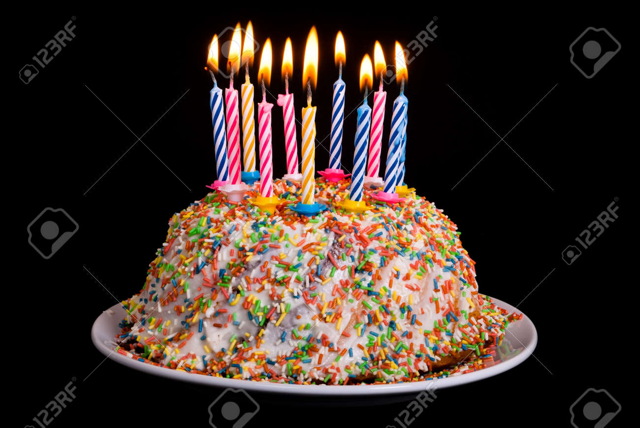 a cake with many coloured candles before black background Stock Photo - 10198984