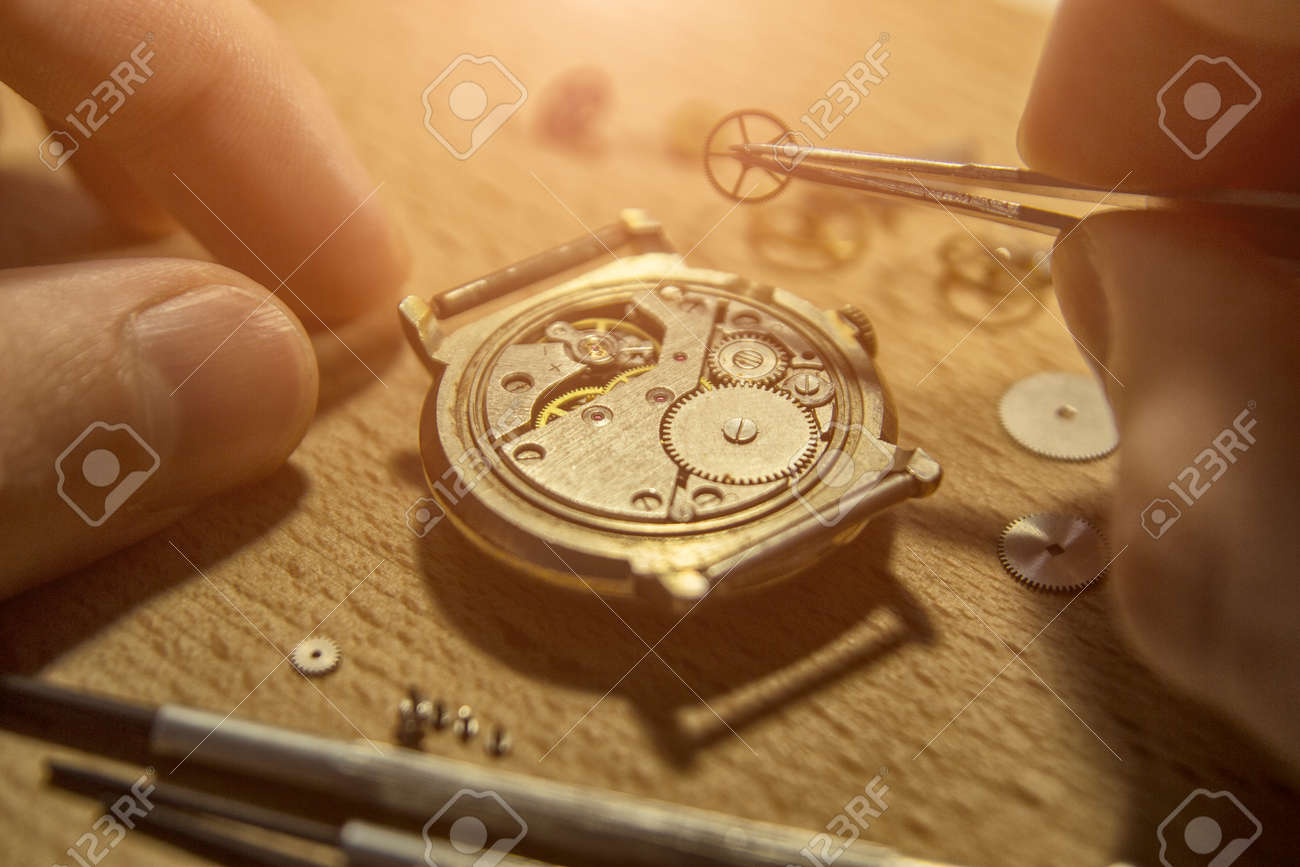 Watchmaker is repairing the mechanical watches in his workshop - 93254296