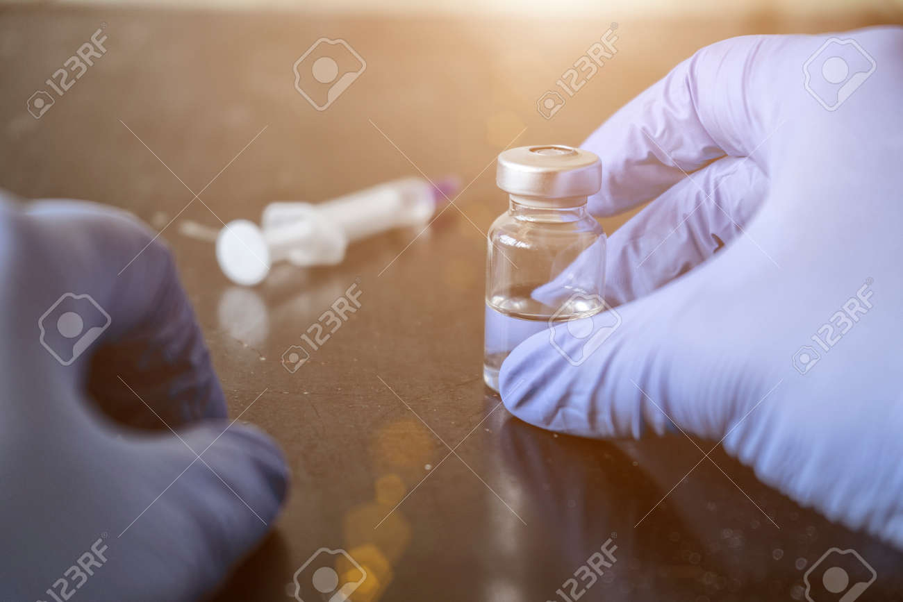 Doctor fills a syringe from an ampoule - 151622216