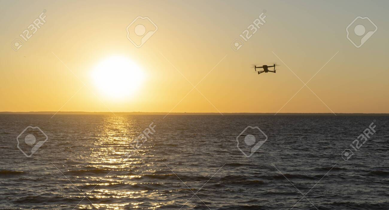 Quadcopter in the sky over the sea - 153349505