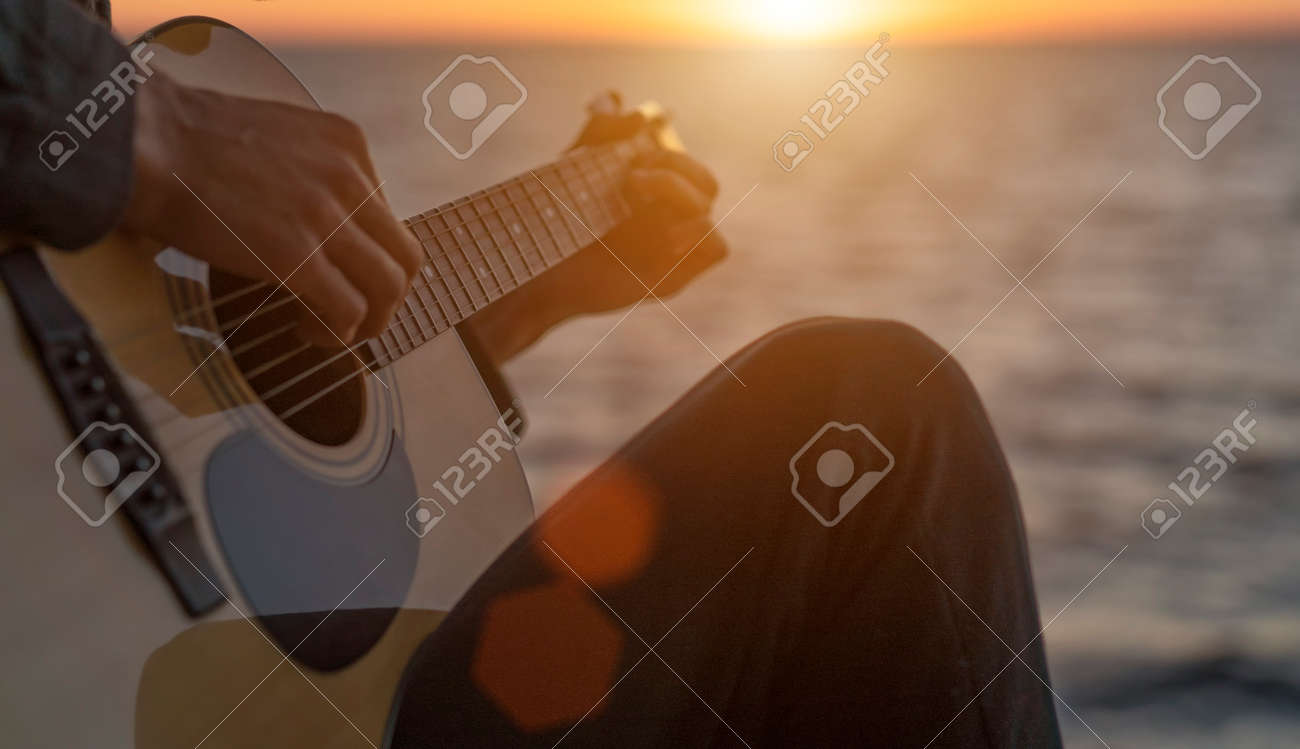 Guy plays guitar at sunset - 153349563