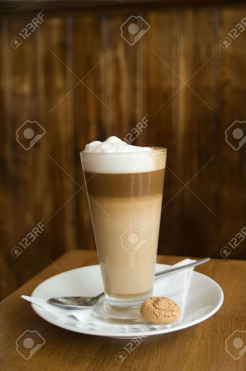 Cafe Latte in a clear glass with an almond cookie, agains dark brown wood background Stock Photo - 2940042