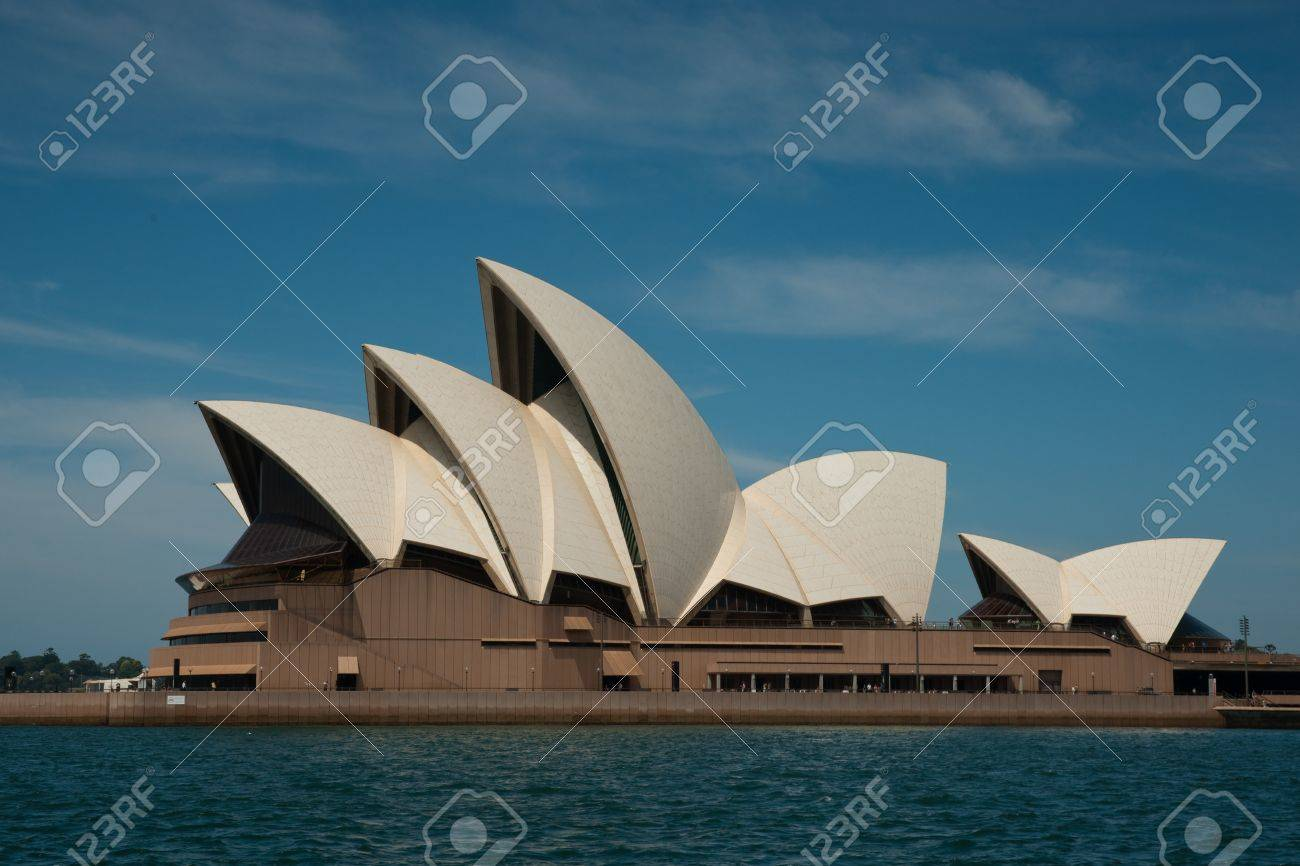 Sydney, Australia - 19 February 2011 : Side view of the Sydney Opera House from the harbour, against a blue sky with some white clouds Stock Photo - 10007473