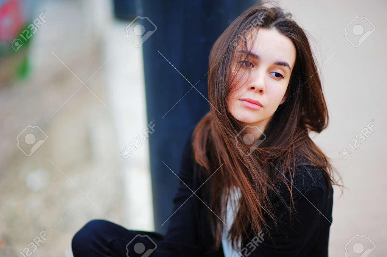 Archivio Fotografico - Giovane ragazza bruna dai capelli lunghi è seduta  tagliata ai capelli del vento e una vista malinconica sulla strada in un  giorno ... 8578394b38ca