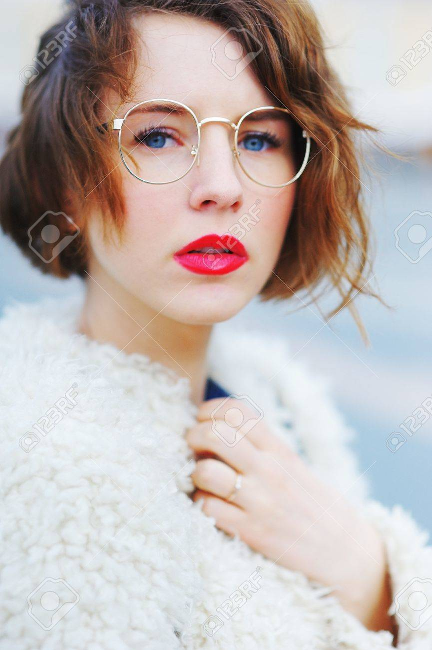 96038803db Stock Photo - Wonderful portrait of cute charming girl with beautiful eyes  and round glasses with her mouth slightly open in a white cardigan on  blurred ...