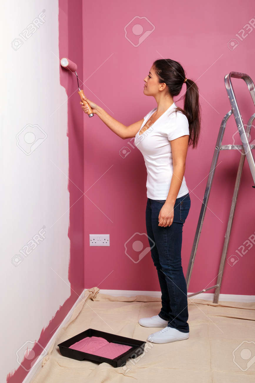 Woman Home Decorating an attractive young woman decorating the wall of her new home
