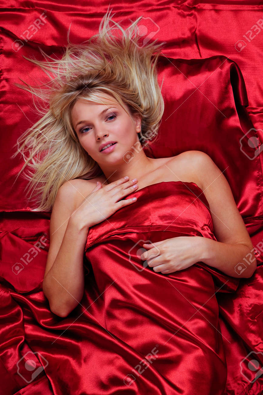 A Beautiful Young Blonde Woman In A Bed Of Red Silk Sheets, Overhead Shot.