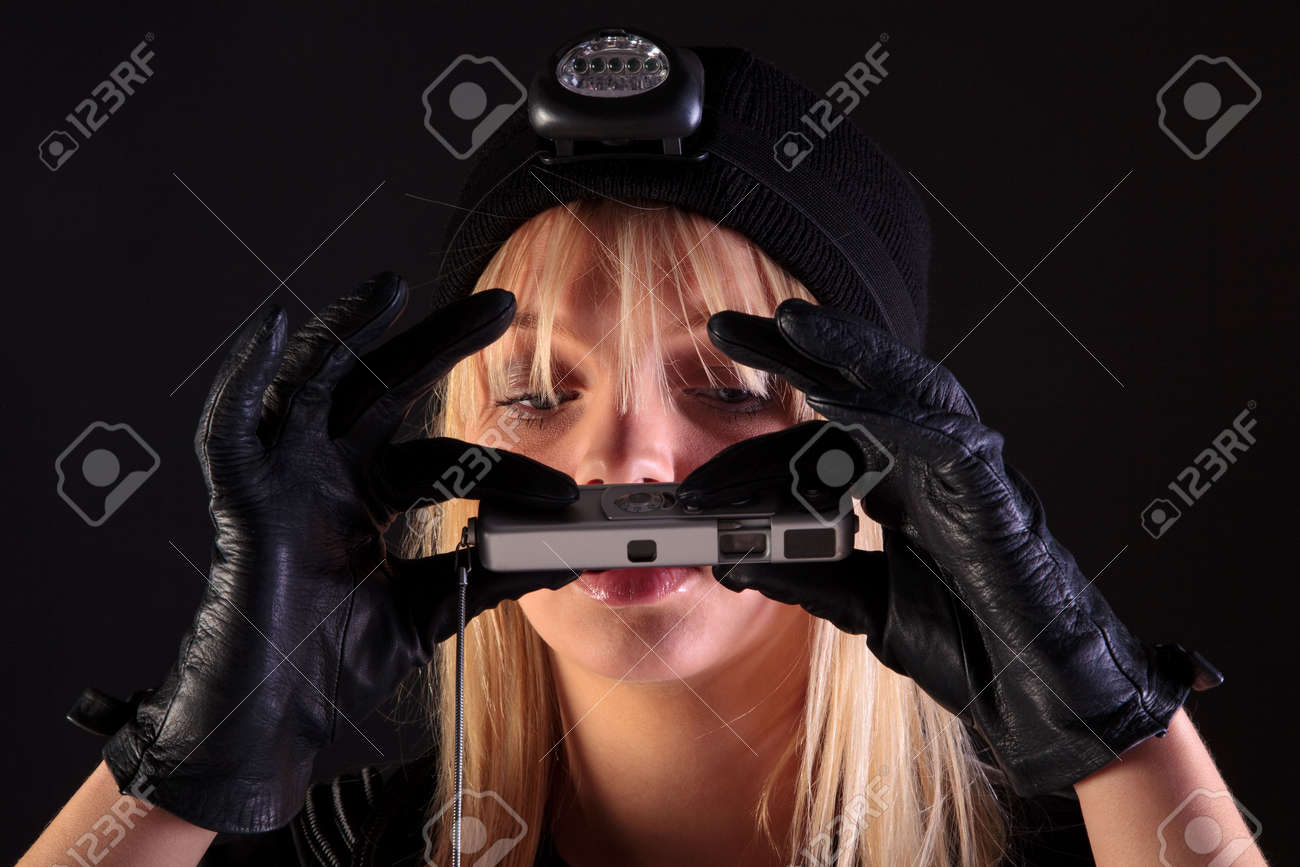 Blond woman cat burglar taking a photo with a spy camera Stock Photo - 5179536