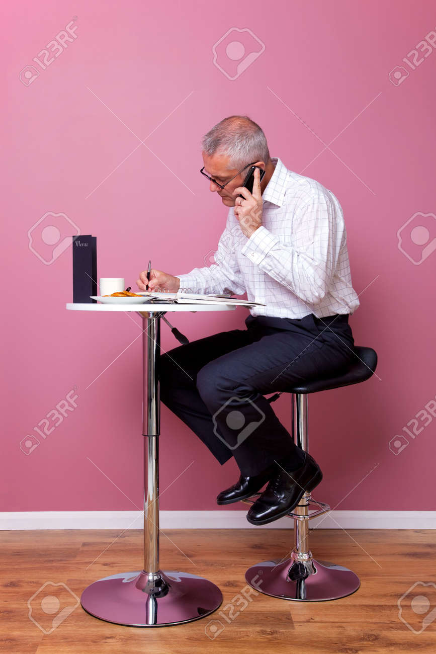 Businessman in smart casual attire sat on a bar stool in a cafe working through his lunch break. Stock Photo - 5663005