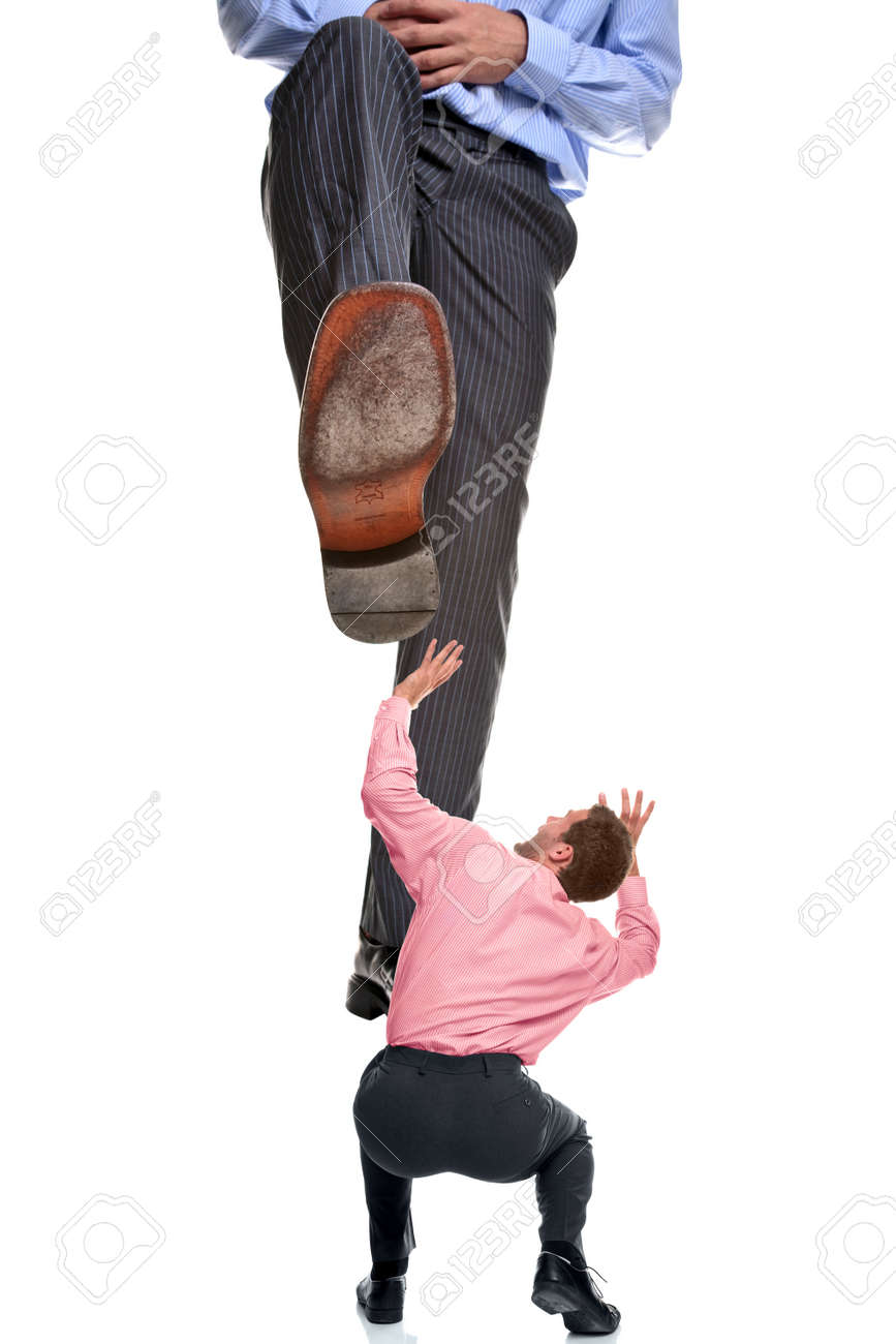 A businessman about to be stepped on by a giant foot, isolated on a white background. Stock Photo - 5955315