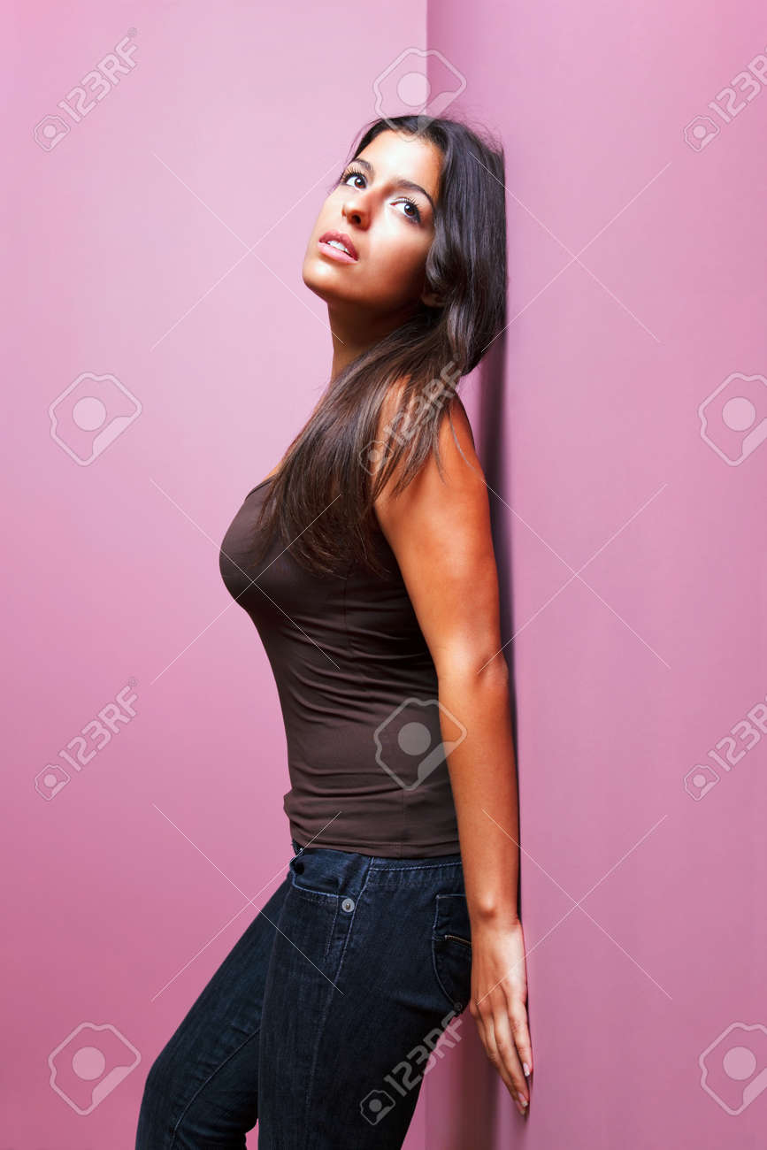 An attractive brunette woman in casual clothing leaning with her back against a wall in the corner of a room. Possible uses could include romance or listening related themes. Stock Photo - 7056913
