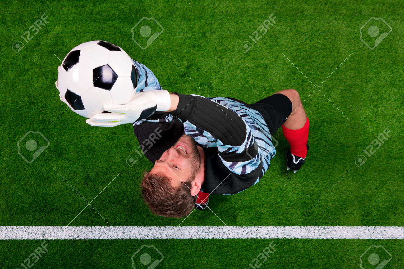 Overhead photo of a football goalkeeper jumping in the air saving the ball on the line. Focus point is on his face. Stock Photo - 11020184