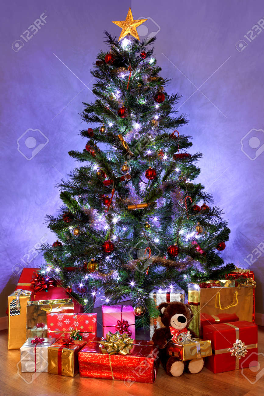 Photo of a Christmas tree with decorations and fairy lights surrounded by presents on a wooden floor. The teddy bear is generic and is not a known brand. Stock Photo - 11329675
