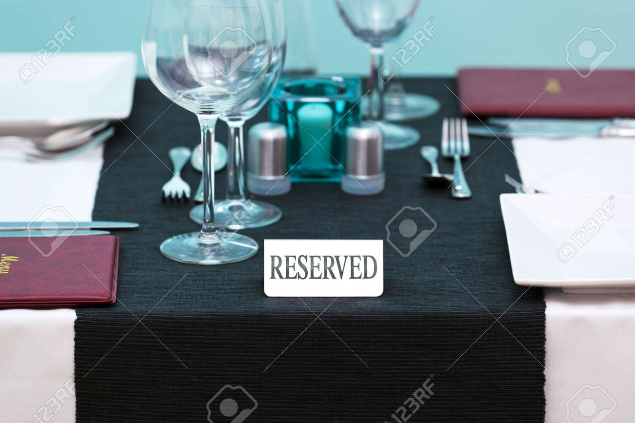 Photo of a Reserved sign on a restaurant table with menus on the side and place settings for two people. Stock Photo - 12194716